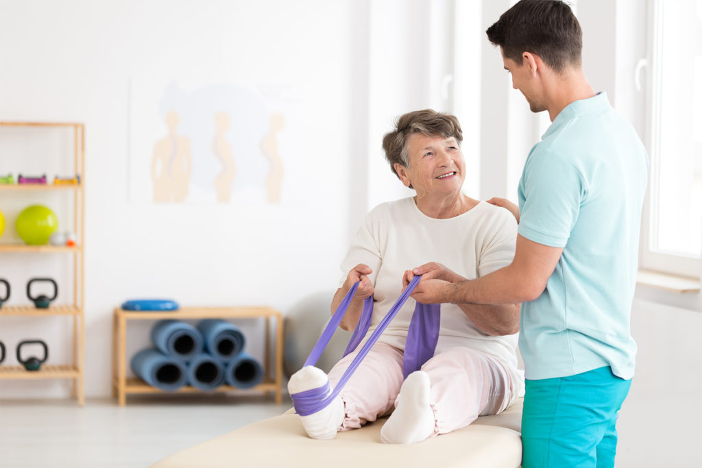 Therapist assisting elderly woman exercising with stretch band