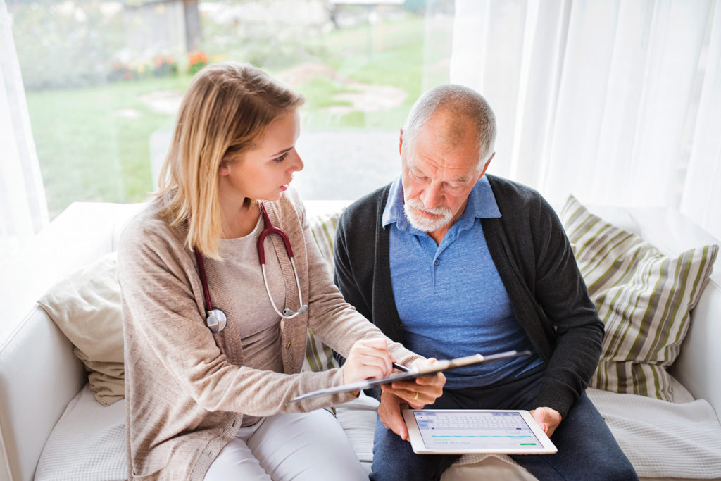 Therapist and a senior man with tablet during home visit