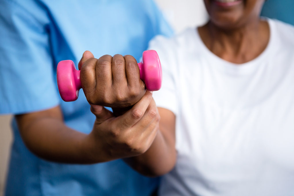 Closeup of therapist guiding senior woman in lifting dumbbell
