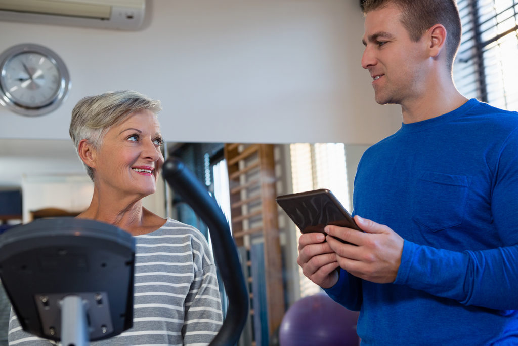 Therapist interacting with senior woman while exercising on exercise bike